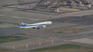AX120_068E - 6K stock footage aerial video of a commercial jet approaching and landing at JFK Airport in Autumn