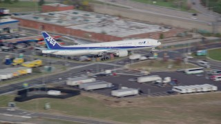 AX120_069 - 6K stock footage aerial video of a commercial jet descending toward JFK Airport in Autumn