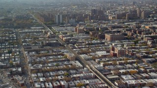 AX120_077E - 6K stock footage aerial video of row houses, elevated rail, and public housing in Autumn, Brooklyn, New York City