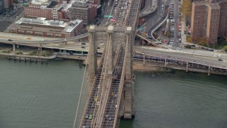AX120_136 - 6K stock footage aerial video orbit heavy traffic on the Brooklyn Bridge, New York City
