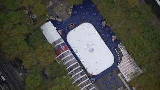 AX120_184 - 6K stock footage aerial video of a bird's eye orbit of the ice skating rink at Bryant Park, Midtown, New York City