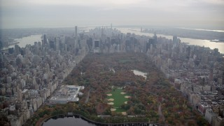 AX120_212 - 6K stock footage aerial video approach the Met and Midtown high-rises from Central Park in Autumn, New York City