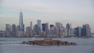 AX120_260 - 6K stock footage aerial video orbiting Ellis Island and Lower Manhattan skyline in Autumn, New York City