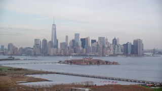 AX120_263 - 6K stock footage aerial video of Lower Manhattan skyline and Ellis Island in Autumn, New York City