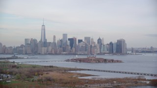 AX120_264 - 6K stock footage aerial video of Lower Manhattan and Ellis Island seen from New Jersey in Autumn, New York City