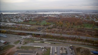 AX120_265 - 6K stock footage aerial video approach a Jersey City cemetery by a freeway in Autumn, New Jersey