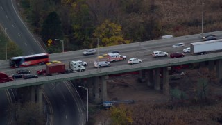 AX121_007E - 5.5K stock footage aerial video track ambulance on busy freeway at Sunset in Autumn, Bayonne, New Jersey