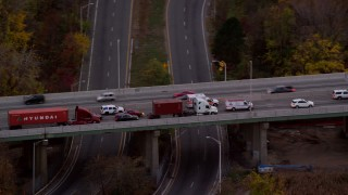 AX121_009 - 6K stock footage aerial video of an ambulance passing heavy freeway traffic at twilight, Bayonne, New Jersey