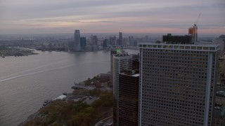 AX121_034 - 6K stock footage aerial video fly around skyscraper to reveal Downtown Jersey City from Lower Manhattan at twilight