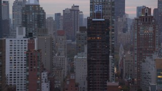 AX121_058 - 6K stock footage aerial video pass by streets and Upper East Side skyscrapers at twilight in New York City