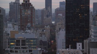 AX121_060 - 6K stock footage aerial video flyby high-rises and busy streets on Upper East Side at twilight in New York City