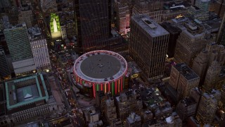 AX121_085 - 6K stock footage aerial video orbit Madison Square Garden at twilight in New York City