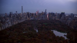 AX121_098 - 6K stock footage aerial video of Midtown skyscrapers seen from The Lake in Central Park at twilight, New York City