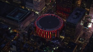 AX121_129 - 6K stock footage aerial video orbit of Madison Square Garden at twilight in Midtown Manhattan, New York City