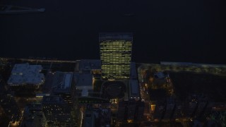 AX121_139 - 6K stock footage aerial video tilt to a bird's eye view of United Nations at Night in New York City