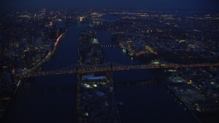 AX121_141 - 6K stock footage aerial video orbit Queensboro Bridge and Roosevelt Island at Night in New York City