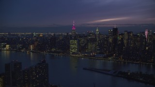 AX121_142 - 6K stock footage aerial video of UN Building and Midtown seen from Queens at Night in New York City