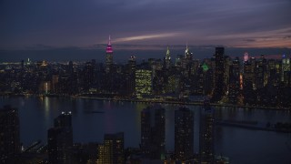 AX121_143 - 6K stock footage aerial video wide view of UN Building and Midtown seen from Queens at Night in New York City