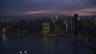 AX121_144 - 6K stock footage aerial video approach UN Building in Midtown at Night from East River, New York City