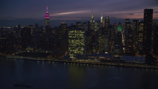 AX121_145 - 6K stock footage aerial video approach the UN Building in Midtown from the river at Night in New York City