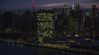 AX121_146 - 6K stock footage aerial video approach and orbit the UN Building at Night in New York City