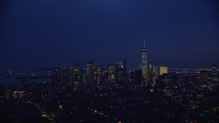 AX121_153E - 5.5K stock footage aerial video approach Lower Manhattan skyline at Night in New York City
