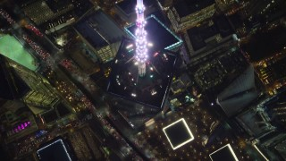 AX121_175 - 6K stock footage aerial video approach top spire of Freedom Tower and tilt to bird's eye view at Night in NYC