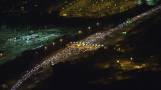 AX121_198 - 6K stock footage aerial video orbit heavy traffic at a Toll Booth at Night in New Jersey