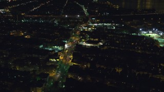 AX121_201 - 6K stock footage aerial video orbit homes and a busy street near a strip mall at Night, Jersey City, New Jersey