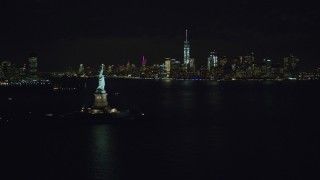 AX122_012 - 6K stock footage aerial video of the Statue of Liberty and Lower Manhattan skyline at Night in NYC