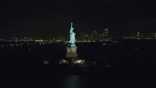 AX122_013 - 6K stock footage aerial video orbit the front of the Statue of Liberty at Night in New York