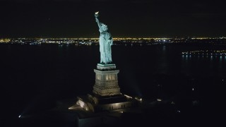 AX122_015 - 6K stock footage aerial video orbiting the Statue of Liberty at Night in New York