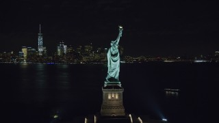 AX122_021 - 6K stock footage aerial video orbit torch side of the Statue of Liberty at Night in New York