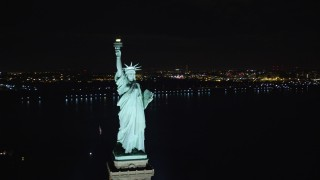 AX122_023 - 6K stock footage aerial video of the front of the Statue of Liberty at Night in New York