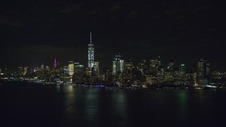 AX122_025 - 6K stock footage aerial video approach the Lower Manhattan skyline at Night in New York City