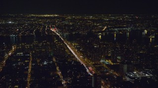 AX122_051 - 6K stock footage aerial video orbit heavy traffic on Delancey Street to Williamsburg Bridges at Night in Lower East Side, NYC