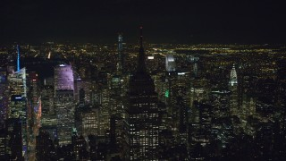AX122_085 - 6K stock footage aerial video orbit the unlit rooftop of Empire State Building at Night in Midtown, New York City