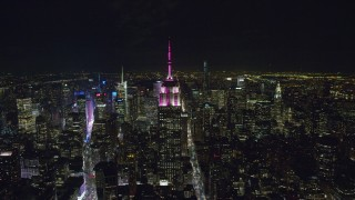 AX122_090 - 6K stock footage aerial video orbit of the Empire State Building at Nighttime in Midtown Manhattan, NYC