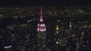 AX122_100 - 6K stock footage aerial video circle the Empire State Building with pink and white lights at Night, Midtown, NYC