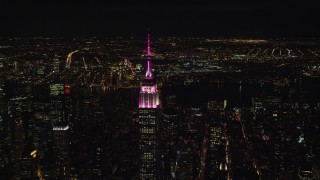 AX122_102 - 5.5K stock footage aerial video circle the Empire State Building with pink and white lights at Nighttime, Midtown, NYC