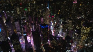 AX122_125E - 5.5K stock footage aerial video orbit skyscrapers around Times Square at Night in Midtown Manhattan, New York City