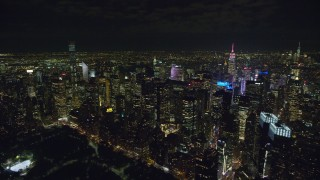 AX122_132 - 6K stock footage aerial video of a flyby of Midtown Manhattan high-rises at Night in NYC