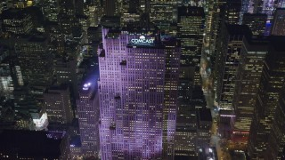 AX122_137 - 6K stock footage aerial video of approaching Rockefeller Center at Night in Midtown Manhattan, New York City