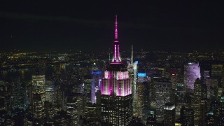 AX122_155 - 6K stock footage aerial video orbit of the Empire State Building at Night in Midtown Manhattan, New York City