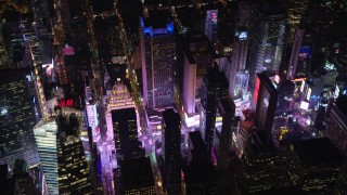 AX122_197E - 5.5K stock footage aerial video orbit skyscrapers around Times Square at Night in Midtown Manhattan, New York City