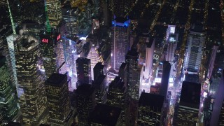 AX122_198 - 6K stock footage aerial video orbit of Times Square and skyscrapers in Midtown Manhattan, New York City at Night