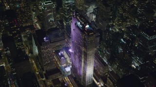 AX122_202 - 6K stock footage aerial video of circling around Rockefeller Center with ice rink at Night in Midtown, NYC