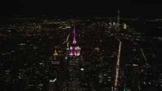 AX122_213 - 5.5K stock footage aerial video orbit Empire State Building with view of Lower Manhattan at Night, New York City