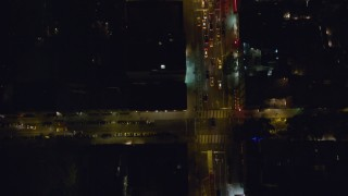 AX122_238 - 6K stock footage aerial video of a bird's eye of cars and traffic stop on 2nd Avenue at Night in East Village, New York City