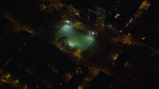 AX122_239 - 6K stock footage aerial video orbit a soccer field on the Lower East Side at Night in New York City